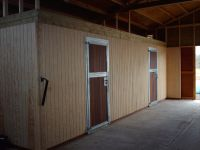Metal framed tack room doors with hardwood infill. Set into vertical T&G boarding.