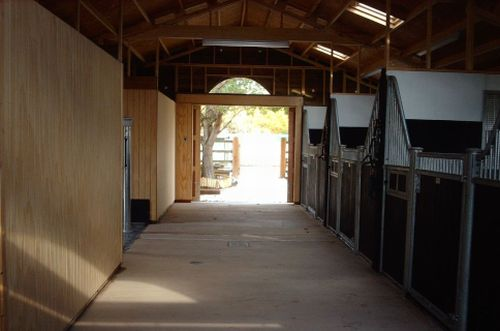 An internal view of a Warwick Buildings American Barn designed using Victorian style stable fronts and controllable roof ventilation. A stall area is located between a tackroom to one side and a utility room to the other