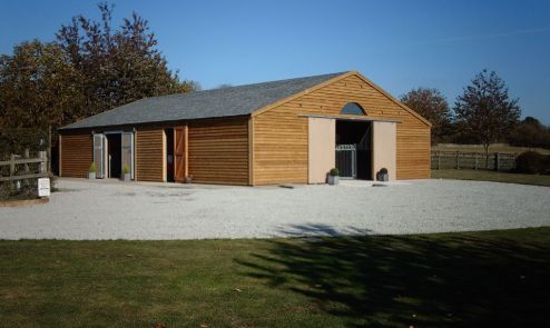 An external view of American Barn in Feather Edge Boarding featuring Ultra Profile Grey Felt Tiles. Several door positions and over stable adjustable roof ventilation, provides controllable air movement inside the building